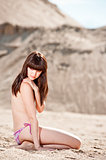 Young thin girl posing topless on the sand dunes on the background