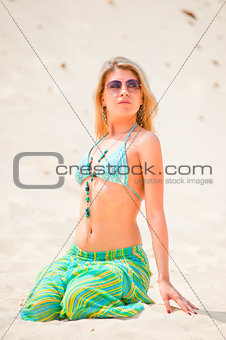 Young girl in sunglasses sitting on the sand.