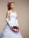 Marriage. Fashionable Bride Blonde in Bridal White Dress and Unusual Bouquet of Flowers