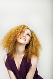 Lifestyle. Radiant Happy Woman with Curly Golden Hairs smiling. Positive Emotions