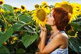 woman on blooming sunflower field