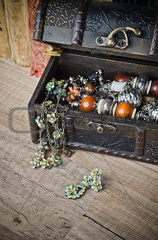 casket with jewelry and old book on a wooden surface