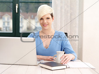 Happy female student working on laptop