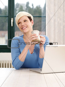 Smiling female working on a laptop