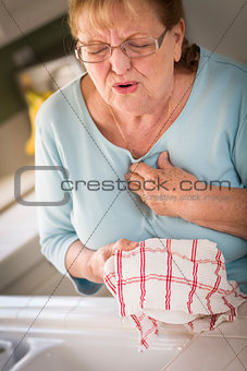 Senior Adult Woman At Sink With Chest Pains