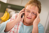 Shocked Senior Adult Woman on Cell Phone in Kitchen