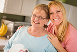 Senior Adult Woman and Young Daughter Portrait in Kitchen