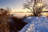 canal and wooden fence in snow at sunrise