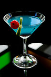 blue cocktail with cherry and lime