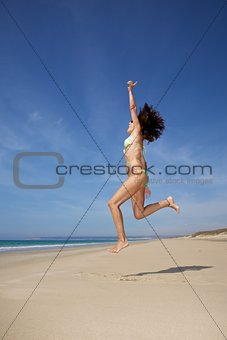 bikini woman jumping at beach