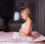 young pregnant woman sitting on bed at home