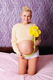 beautiful young pregnant  woman at home holding a daisy