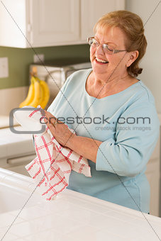 Senior Adult Woman Drying Bowl At Sink in Kitchen