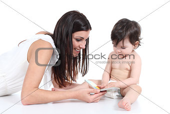 Attractive happy mother showing a book to her daughter