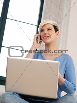 Pretty female sitting with laptop and smartphone