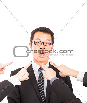 all hands pointing towards surprised businessman
