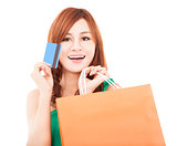 smiling young woman holding credit card with shopping bag