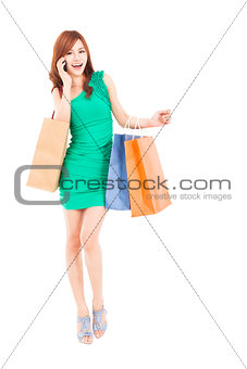 full length of asian woman with shopping bags talking on the pho