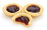 Three jam tarts, one with a bite taken