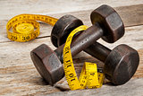 iron dumbbells and measuring tape
