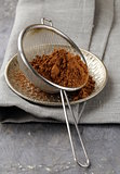 cocoa powder in a metal sieve with a gray background