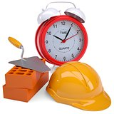 Bricks, hard hat and alarm clock