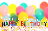 Happy birthday lit candles on colorful balloons background