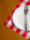 white plate and fork on wooden table with red checked tablecloth