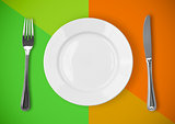 Knife, plate and fork on colorful background