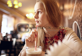 Girl is looking through the window in cafe.