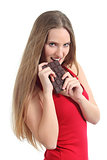 Beautiful woman in red eating a chocolate bar