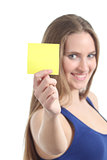 Woman holding and showing a blank yellow paper note