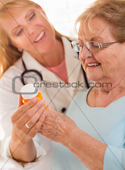 Female Doctor or Nurse Explaining Prescription to Senior Adult W
