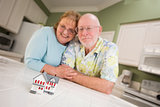 Senior Adult Couple Gazing Over Small Model Home on Counter