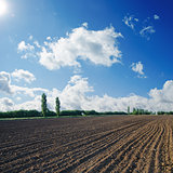 black plowed field under blue sky with sun