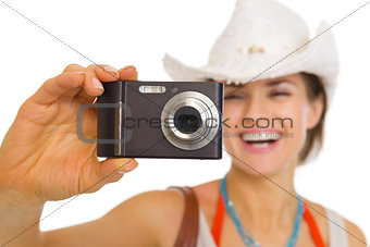 Closeup on camera in hand of young beach woman in hat
