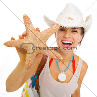 Happy young beach woman in hat showing starfish
