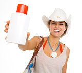 Happy young beach woman in hat showing sun block creme
