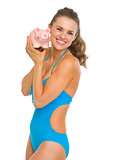 Happy young woman in swimsuit showing piggy bank