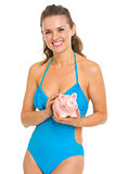 Smiling young woman in swimsuit holding piggy bank