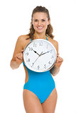 Happy young woman in swimsuit showing clock