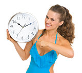 Smiling young woman in swimsuit pointing on clock