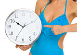 Closeup on young woman in swimsuit pointing on clock