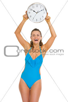 Smiling young woman in swimsuit showing clock