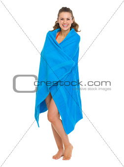 Happy young woman in swimsuit bundle up in towel