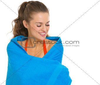 Portrait of happy young woman in swimsuit wraped in towel