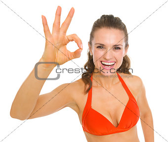 Happy young woman in swimsuit showing ok gesture