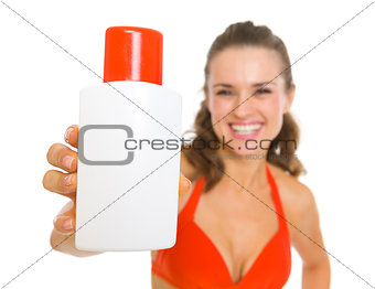 Smiling young woman in swimsuit showing sun block creme
