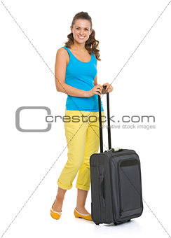 Happy young woman with wheel bag going on vacation