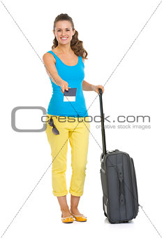 Smiling young tourist woman with wheel bag giving passport and t